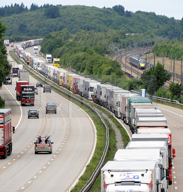 © Licensed to London News Pictures. 28/07/2015<br /> Operation stack lorries between J8 and J9 for Ashford on the M20. Highspeed Javelin train in picture (r)<br /> Operation stack is back on the M20 in Kent.<br /> Just days after Operation Stack was taken off the M20, it was brought back in the early hours of this morning.<br /> The authorities are blaming a heavy volume of traffic heading towards the Port of Dover and Eurotunnel and the continued disruption in Calais.<br /> The coast-bound carriageway between junctions 8 and 9 is closed to allow lorries to park, but the slip roads at junctions 9, 10 and 12 and 13 have also been shut. <br /> <br /> (Byline:Grant Falvey/LNP)