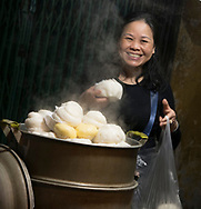 A woman selling steaming dumplings in the Old Quarter, Hanoi, Vietnam, Southeast Asia