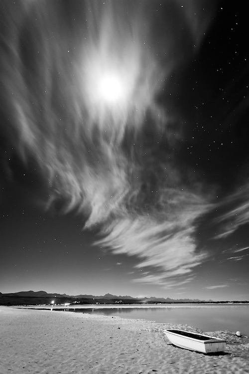 Full moon, stars and row boat at Plettenberg Bay lagoon beach, South Africa.