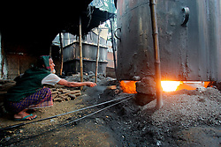 BANGLADESH SIRAJGANJ RADHUNIBARI 31JAN07 - A labourer fuels fire underneath a huge tank boiling raw cotton yarns. Records of an indigenous weaving industry based on handlooms producing cotton fabrics date back to the 13th century in this area...jre/Photo by Jiri Rezac..© Jiri Rezac 2007..Contact: +44 (0) 7050 110 417.Mobile:  +44 (0) 7801 337 683.Office:  +44 (0) 20 8968 9635..Email:   jiri@jirirezac.com.Web:    www.jirirezac.com..© All images Jiri Rezac 2007 - All rights reserved.