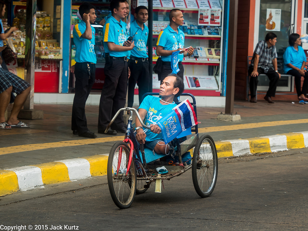 16 AUGUST 2015 - BANGKOK, THAILAND:  A legless man rides his custom bicycle decorated with a Thai flag on Phayathai Road during the ''Ride for Mom.'' More than 100,000 people across Thailand participated in the Bike For Mom event in honor of Queen Sirikit, who celebrated her 83rd birthday August 12. In Bangkok, the ride was led by His Royal Highness Crown Prince Maha Vajiralongkorn, the Crown Prince of Thailand and Sirikit's only son. Queen Sirikit, who is in poor health and living in a hospital, was unable to attend the bike ride.    PHOTO BY JACK KURTZ