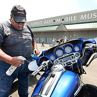 Adam Robison | BUY AT PHOTOS.DJOURNAL.COM<br /> Gary Warren, of Mount Juliet Tennessee, cleans up his Harley in the parking lot of the Tupelo Automibile Museum as he and other bikers made their way through Tupelo Wednesday.