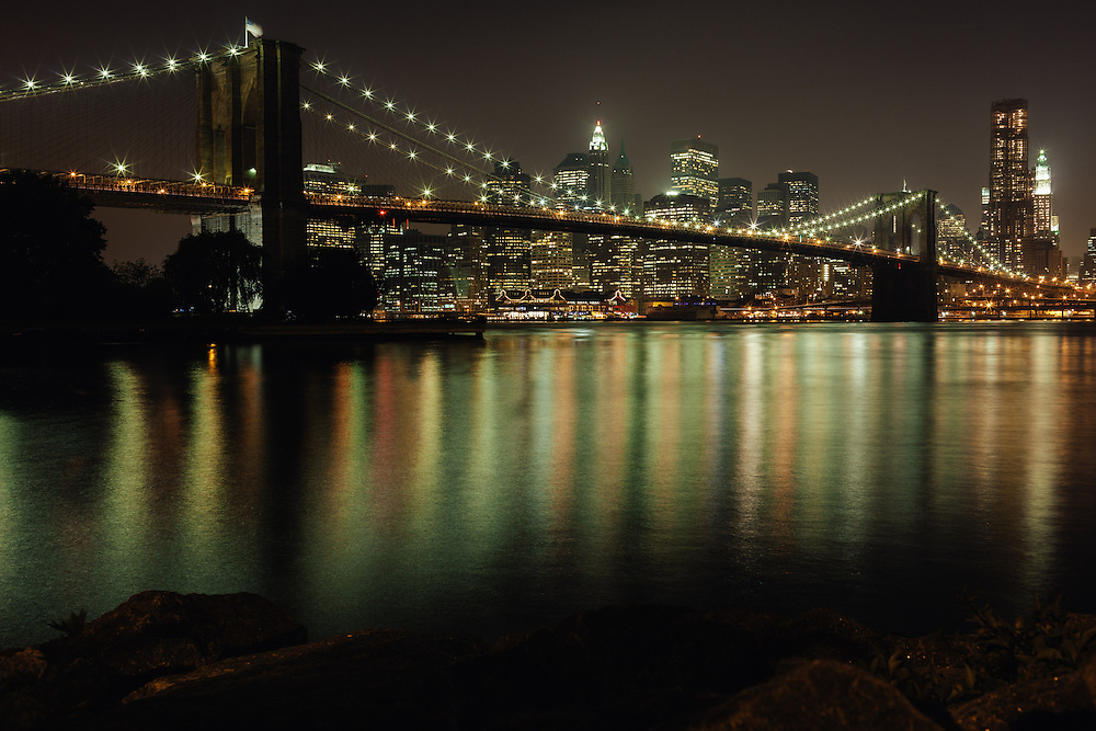 A view of Manhattan at night with the Brooklyn Bridge in the foreground.