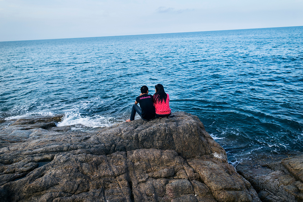 Two lovers sit on rocks and contemplate the late afternoon sea at Lad Koh viewpoint in Koh Samui, Thailand.