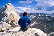 Climber looking out from the summit of Bear Creek Spire, John Muir Wilderness, Sierra Nevada Mountains, California