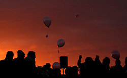 © Licensed to London News Pictures. <br /> 16/12/2014. <br /> <br /> Hartlepool, United Kingdom<br /> <br /> Balloons with the names of those killed during the bombardment are released into the morning sky by children from St Aidan's Primary School during a sunrise memorial event to commemorate the bombardment of Hartlepool by German warships during World War One. During the bombardment 130 civilians were killed and more than 500 were wounded. The Headland's Heugh Gun Battery returned fire in what was the only battle to be fought on British soil during World War One, and one of the Battery's soldiers, Theo Jones of the Durham Light Infantry, became the first British soldier to be killed by enemy action on home ground in the war.<br /> <br /> Photo credit : Ian Forsyth/LNP