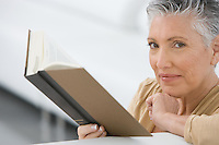 Middle-aged woman reading book on sofa