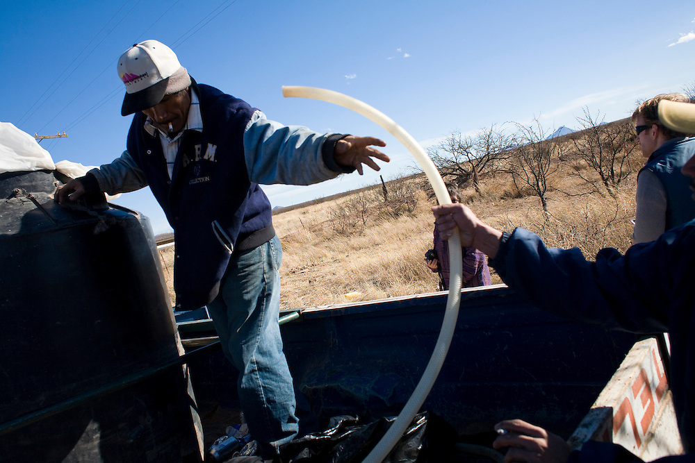 Esteban Perez, a volunteer with the Migrant Resource Center, reaches for a hose while filling water tanks in the desert near Naco, Sonora, Mexico, on Wednesday, Jan. 30, 2008. MRC is a bi-national project of Citizens for Border Solutions (Bisbee, AZ) and Iglesia del Camino (Naco, Mexico), with support of other organizations and individuals.