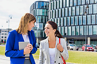 Businesswomen walking while talking outside office building