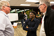 """100state board member Greg St. Fort, center, chats with attendees during the 100state """"Problem Solving Soirée"""" on January 11, 2017. The event kicked off the opening of the entrepreneurial coworking space on the 6th floor of 316 West Washington Avenue in Madison."""
