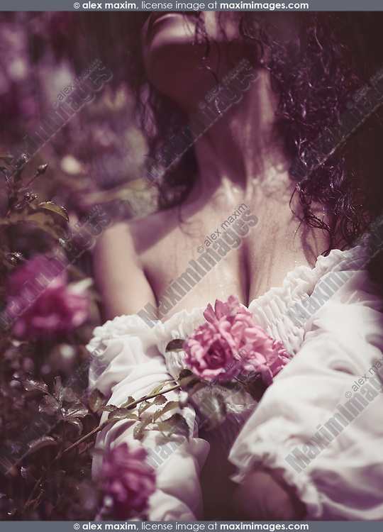 Sensual romantic closeup portrait of rain falling an a beautiful woman chest soaking wet her long dark hair and white summer dress with pink roses growing in front of her