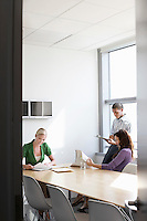 Three office workers in conference room