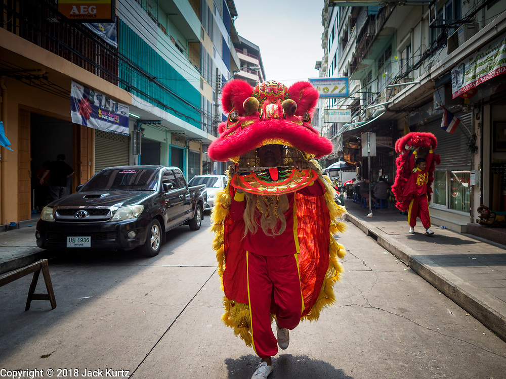 """15 FEBRUARY 2018 - BANGKOK, THAILAND: Chinese """"lion dancers"""" walk through Bangkok's Chinatown neighborhood looking soliciting customers. The dancers go door to door looking for people who pay them as a form of merit making. Lunar New Year, also called Tet or Chinese New Year, is 16 February this year. The coming year will be the Year of the Dog. Thailand has a large Chinese community and Lunar New Year is widely celebrated in Thailand, especially in Bangkok and large cities with significant Chinese communities.     PHOTO BY JACK KURTZ"""