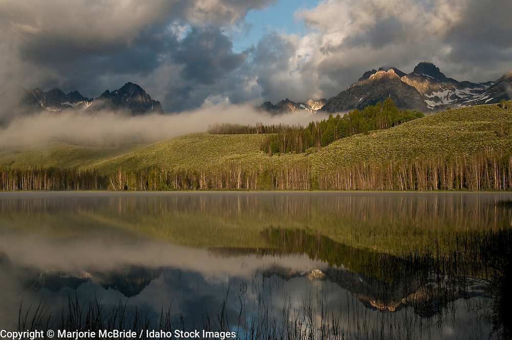 Sunrise on a cloudy morning after a storm reflecting clouds and the Sawtooth mountains in Little Red Fish Lake near Stanley, Idaho.