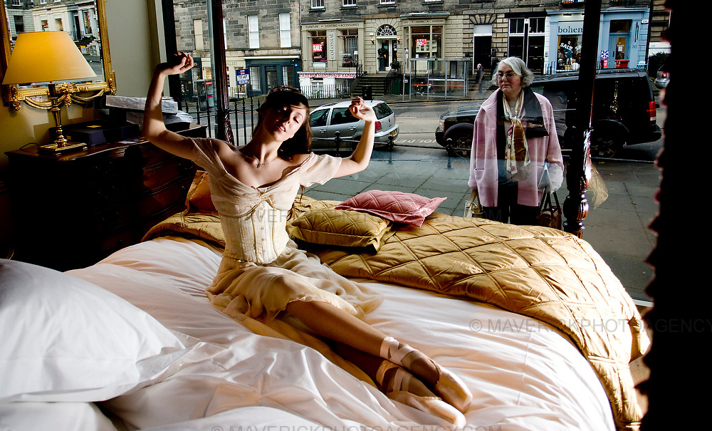 "A shopper looks through a bed shop window as Scottish Ballet dancer Lauren Bryden wakes up, dressed in character as Princess Aurora from the the news scottish ballet production ""The Sleeping Beauty""..7/1/2009.Picture Michael Hughes/Maverick"