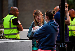 © Licensed to London News Pictures. 23/06/2017. London, UK. A woman carries a newborn baby as residents are evacuated from the Taplow block of the Chalcots Estate in Camden after it failed a fire inspection because of combustable cladding. Prime Minister Theresa May has told Parliament that up to 600 high rise tower blocks may have similar cladding to that found in Grenfell Tower, which went on fire last week, in which as many as 79 residents are thought to have perished Photo credit: Ben Cawthra/LNP