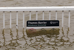 © Licensed to London News Pictures. 10/02/2020. London, UK. A Thames barrier sign on railings is seen underwater during flooding at the Thames Barrier in London which is seen closed this afternoon at high tide to protect the capital from flooding during Storm Ciara. The Thames Barrier prevents the floodplain of most of Greater London from being flooded by exceptionally high tides and storm surges.  Photo credit: Vickie Flores/LNP