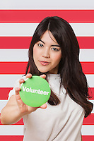 Portrait of young woman holding out volunteer badge against American flag