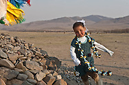 Mongolia. little girl turning around a buddhist stone OVO ,   , , in a family, in a ger camp near the village of Gatchurt.  Ulan Baatar ULN - Mongolia  Children fashion Deux par Deux collection / petite fille devant un Ovo chamanique, Mode enfant dans une famille , dans un campement de yourtes, pres de Gatchurt  Oulan Bator - Mongolie  / 01D