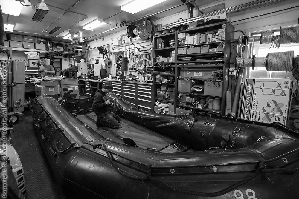 Marine Techs Dave Moore and TR repairing a zodiac in the Boathouse