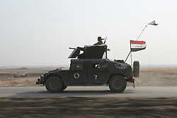October 23, 2016 - Bartella, Nineveh, Iraq - An Iraqi Army Humvee races along a recently liberated stretch of  the Erbil to Mosul highway...Bartella, a mainly Christian town with a population of around 30,000 people before being taken by the Islamic State in August 2014, was captured two days ago by the Iraqi Army's Counter Terrorism force as part of the ongoing offensive to retake Mosul. Although ISIS militants were pushed back a large amount of improvised explosive devices are still being found in the town's buildings. (Credit Image: © Matt Cetti-Roberts/London News Pictures via ZUMA Wire)