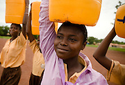 Girls carrying jerry cans of water on their head outside the Zogbeli Junior Secondary School in Tamale, Ghana on Thursday June 7, 2007.