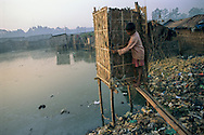 An outhouse perched over a pond serves as the only plumbing in this Bangladeshi slum. For a community to enjoy health, sanitary sewage disposal and clean water are essentials.