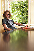 Young man sitting in living room near open window