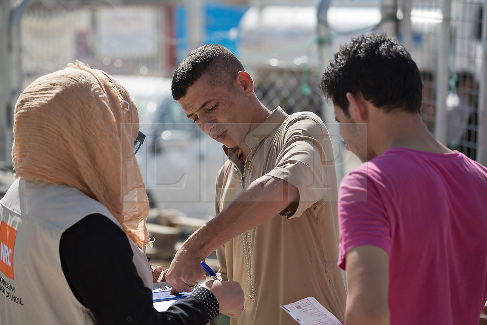 Licensed to London News Pictures. 20/10/2016. A young Iraqi male refugee, recently arrived from areas liberated by the ongoing Mosul Offensive, places his finger print on a form held by an aid worker so that he can receive food and basic hygiene kits.<br /> <br /> The crowded Dibaga camp, housing around 28,000 Sunni Arab refugees, is the main gathering point for new IDPs now fleeing areas where ISIS have been pushed out or are in conflict with the Iraqi Army. Photo credit: Matt Cetti-Roberts/LNP