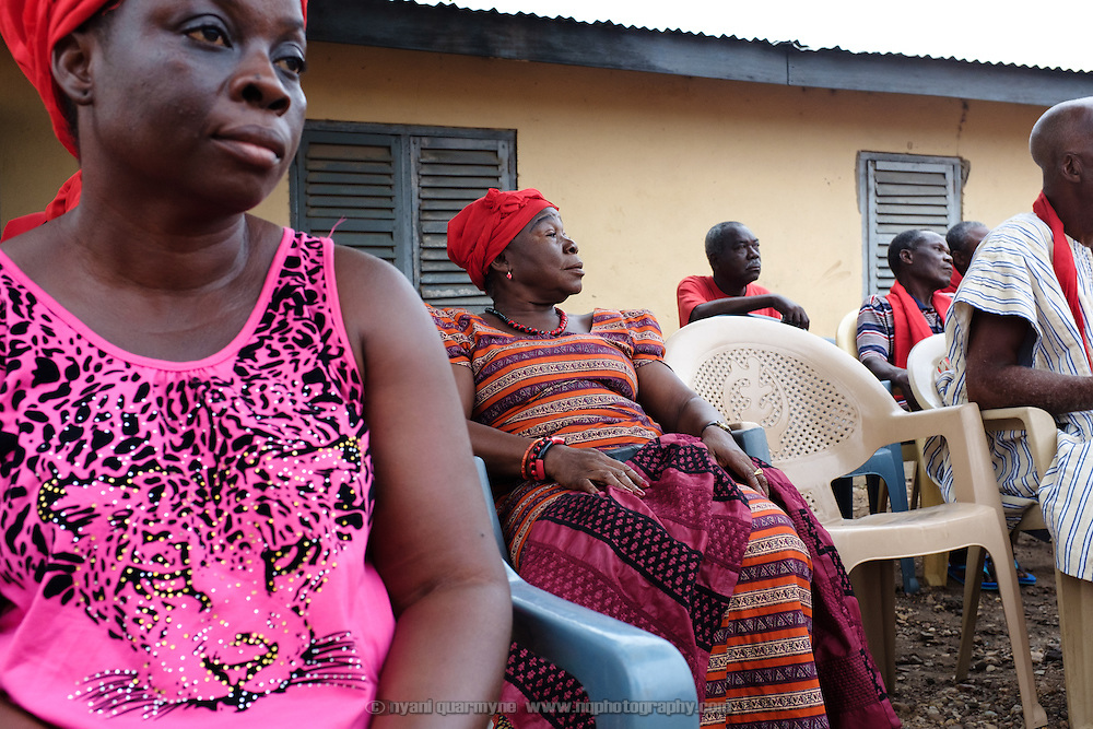 Mama Agblatsu III (second from left), a Queen Mother in Bankoe, a traditional division in the town of Ho in the Volta Region of Ghana, at a weekly early morning meeting of her clan. The clan is an important is an important part of the community's social fabric, and members meet weekly to discuss clan and family matters. The wearing of red signifies that the clan is in mourning - two of their number recently passed away, and funeral matters dominated the meeting.