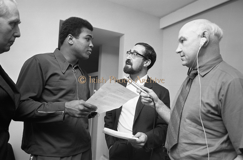 Muhammad Ali In Ireland..1972..14.07.1972..07.14.1972..14th July 1972..A short film on Muhammad Ali in Ireland has been made for showing in the USA before his bout with Al 'Blue'Lewis.The film sponsored by Bord Failte is produced and directed by Mr Louis Marcus.Commentary is provided by Muhammad Ali himself.The project was discussed at Oppermans Country Club Hotel,Kilternan,Co Dublin,where the Ali camp was based...Picture taken as Muhammad Ali goes over his lines with the Director, Mr Louis Marcus.Also in the picture are Mr Tom Sheehy,Bord Failte and sound recordist Mr Peter Hunt..