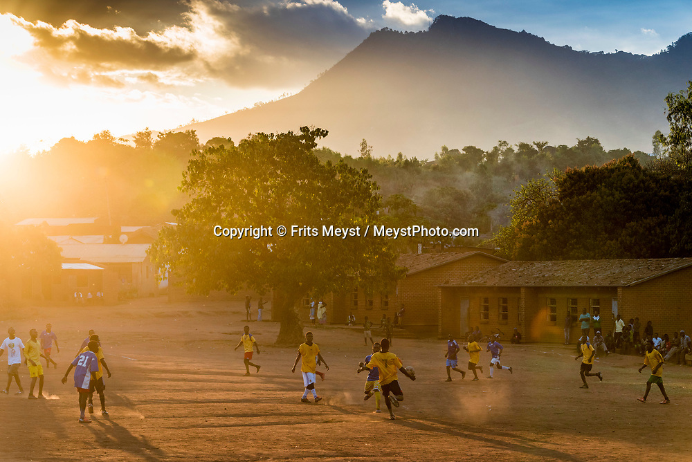 Malawi, July 2017. Soccer players pla a game of football on the dusty village square during sunset. Village life in valleys of The Zomba Massif, a mountain of the Shire Highlands in southern Malawi. Malawi is known for its long rift valley and the third largest lake in Africa: Lake Malawi. Malawi is populated with friendly welcoming people, who gave it the name: the warm heart of Africa. In the south the lake make way for a landscape of valleys surrounded by spectacular mountain ranges. Photo by Frits Meyst / MeystPhoto.com