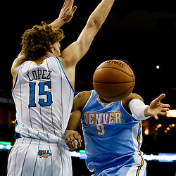 Mar 25, 2013; New Orleans, LA, USA; Denver Nuggets shooting guard Andre Iguodala (9) passes as New Orleans Hornets center Robin Lopez (15) and power forward Ryan Anderson (33) defend during the second half of a game at the New Orleans Arena. The Hornets defeated the Nuggets 110-86. Mandatory Credit: Derick E. Hingle-USA TODAY Sports