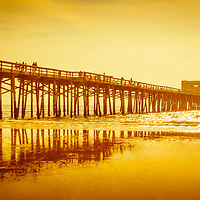 Newport Beach Pier sunset panorama photo. Newport Pier is located along the Pacific Ocean on Balboa Peninsula in Newport Beach, Orange County, California. Panorama photo ratio is 1:3 and has a golden sunset tone.