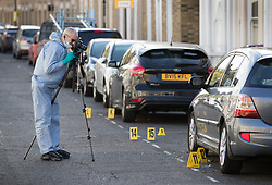 © Licensed to London News Pictures. 30/09/2017. London, UK. A police forensics officer takes photographs of the crime scene after a man was fatally stabbed in Bow, East London. Police were called at 2:30 am on Saturday, 30 September to reports of a disturbance in E3. Officers found a 21-year-old man suffering from stab injuries. He was treated at the scene by London's Air Ambulance before being taken to an east London hospital where he died. Detectives from the Homicide and Major Crime Command are investigating. Photo credit: Peter Macdiarmid/LNP