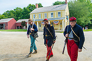 "Old Bethpage, New York, USA. August 30, 2015. At center, ANDREW PREBLE from Long Beach portrays an American Civil War Captain from the 14th Brooklyn Regiment (14th New York State Militia) AKA The Brooklyn Chasseurs, in front of the yellow and white Noon Inn tavern during the Old Time Music Weekend at the Old Bethpage Village Restoration. During their historical reenactments, members of the non-profit 14th Brooklyn Company E wear accurate reproductions of ""The ""Red Legged Devils"" original Union army uniform."