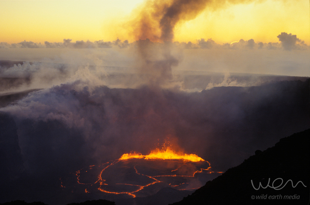 At dawn, a seething lake of molten lava emits a plume of sulfur dioxide from the summit crater of Pu`u O`o volcano, Hawaii, USA