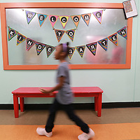 A student hurries past the welcome back sign as she and other students begin the school year.