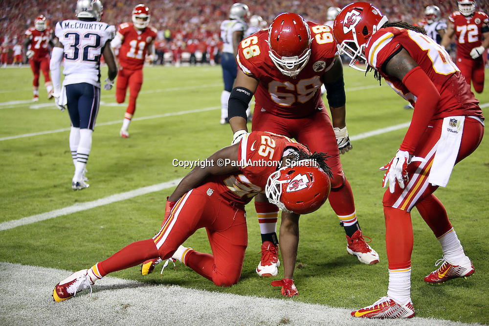 Kansas City Chiefs running back Jamaal Charles (25) holds his leg with an apparent injury after catching a third quarter touchdown pass for a 24-0 lead during the NFL week 4 regular season football game against the New England Patriots on Monday, September 29, 2014 in Kansas City, Mo. The Chiefs won the game 41-14. ©Paul Anthony Spinelli