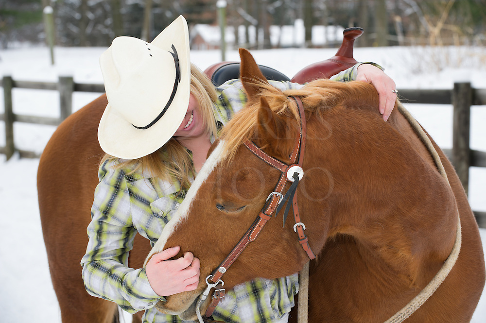 Pretty blonde woman scratching her favorite horse's nose sharing affection and company, twenty-something young causcasian female in winter in casual western dress with cowboy hat and flannel shirt, Pennsylvania, PA, USA.