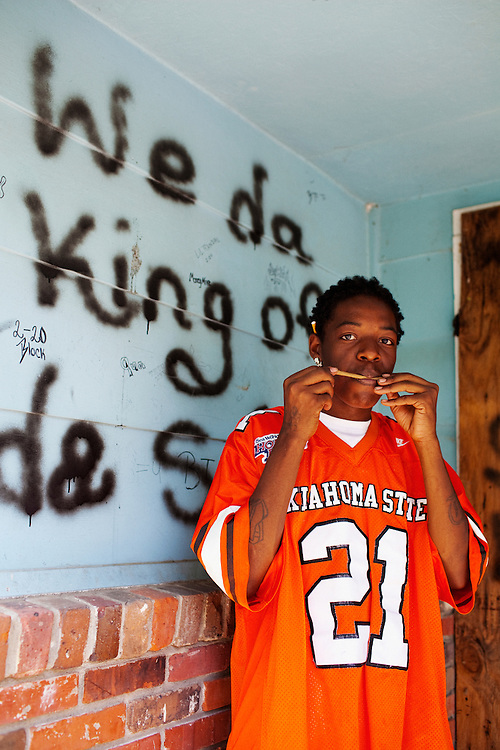 "Dakid Taylor rolls a blunt in the Baptist Town neighborhood of Greenwood, Mississippi on May 25, 2011. Behind him is graffiti, which reads, ""We da King of da Streets."""