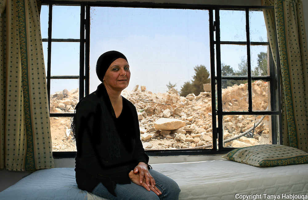 In AL Walaja, West Bank, Siham's home has been demolished twice by Israeli authorities, first for lacking a permit that is extremely difficult for Palestinians to obtain and then for construction of the Barrier. Here she sits in her make shift living room, amidst the rubble of her former home.