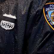 BROOKLYN, NY - JANUARY 4, 2015:  A New York Police Department officer dons a black band across his badge on a rainy morning as officials make preparations for the funeral of NYPD Officer Wenjian Liu outside the Aievoli Funeral Home on 65th Street in Brooklyn. Mr. Liu was killed while on duty in December 2014 in Bedford-Stuyvesant. CREDIT: Sam Hodgson for The New York Times