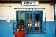 Katy Cherif, 40, waits to get prescription drugs for her twin sons Lusseini and Lacine, both 4 and suffering from malaria and diarrhea, at the pharmacy counter of the Libreville health center in Man, Cote d'Ivoire on Wednesday July 24, 2013.