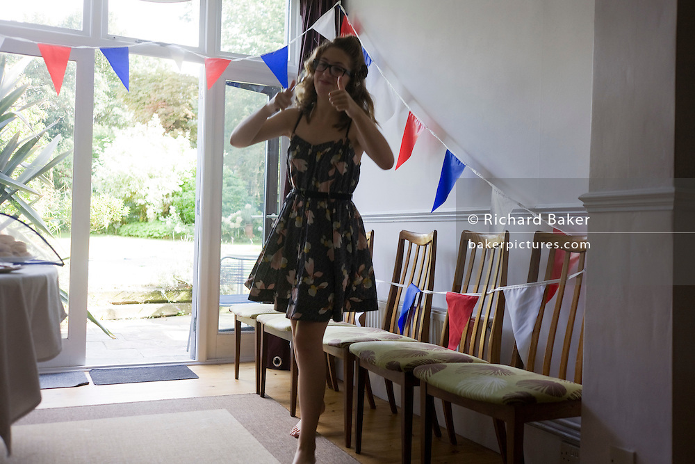 With bunting hanging, a 15 year-old teenager awaits friends in her home before her party.