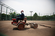 TOKYO, JAPAN - 10 MAY - Minato - A worker preparing the ground of the baseball stadium. May 2010 [FR] Un homme sur une machine prepare le terrain de baseball dans le Minato, proche de roppongi