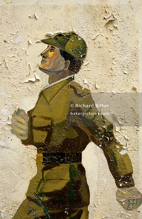 On the edge of an old Soviet parade ground, peeling murals show the physical style of Russian marching techniques seen in this army boot camp in the former East German peninsular called Halbinsel Wustrow near Rostock. For the benefit of recruits or as reminders of Soviet discipline, the picture shows a soldier marching in that unmistakable goose-stepping style reminiscent of the Nazi era, with high forward kicks and a strenuous arm movement to the chest as seen in iconic May Day celebrations in Red Square. Wustrow was once a WW2 German anti-aircraft artillery position then housed civilian refugees before the eventual Soviet occupation of the former DDR during the Cold War, up until 1990 and the fall of communism and the Berlin Wall. The camp was ransacked and all its assets stripped before its desertion that summer and is a reminder of a fallen ideology