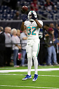 Miami Dolphins running back Kenyan Drake (32) leaps and catches a pass during pregame warmups before the NFL week 8 regular season football game against the Houston Texans on Thursday, Oct. 25, 2018 in Houston. The Texans won the game 42-23. (©Paul Anthony Spinelli)