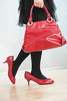 Low section of girl wearing a woman's high heels while carrying red handbag
