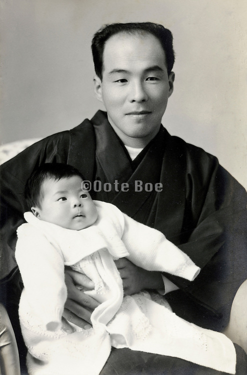 father posing with baby Japan early 1960s